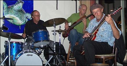 John Hall on drums (left), Lance Jeppesen on bass (center) and Joseph Angelastro on guitar perform Nov. 13 at E Street Cafe in Encinitas. (Photo by Scott Landheer)