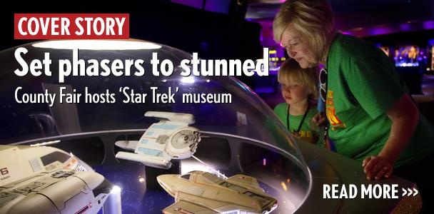 "Becky Cox and her grandson, John Peterson, admire the intricate details of ""Star Trek"" models June 19 used in ""The Next Generation"" TV series. The ships are part of Star Trek: The Exhibition at the San Diego County Fair. (Photo by Scott Allison)"