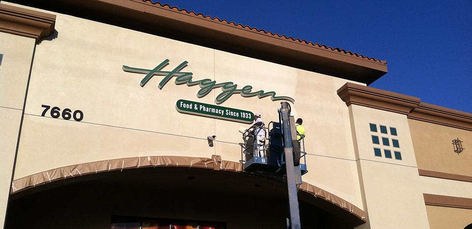 Workers put the finishing touches on a new sign for Haggen market in Carlsbad on March 9. The store, a former Albertsons, is the first for Washington-based Haggen in California. (North Coast Current)