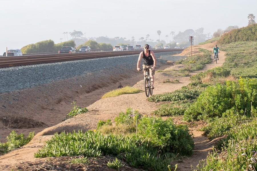 Bicycle riders use a path alongside the rail line in Cardiff on Feb. 14. The area is a possible route for the Coastal Rail Trail. (Photo by Jen Acosta)