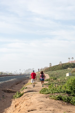 A couple walks along the east side of tracks in Cardiff on Feb. 14. The area is a possible location for a portion of the Coastal Rail Trail. (Photo by Jen Acosta)