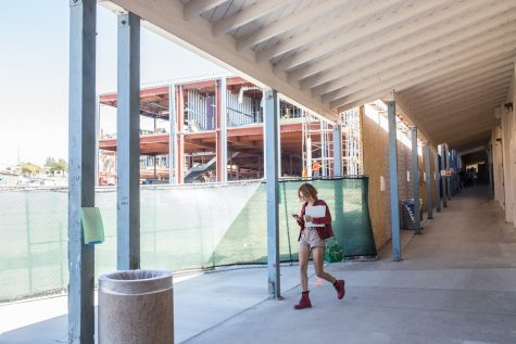 New construction looms over an original classroom building at San Dieguito High School Academy, built in the mid-1930s, as a student heads to class Sept. 15 at the Encinitas campus. (Photo by Jen Acosta)