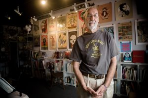 An eclectic mix of art, music and books surrounds Jerry Waddle in Ducky Waddle's Emporium in Leucadia, pictured May 29, 2015. The store is closing this month after 20 years in business. (NCC file photo by Jen Acosta)