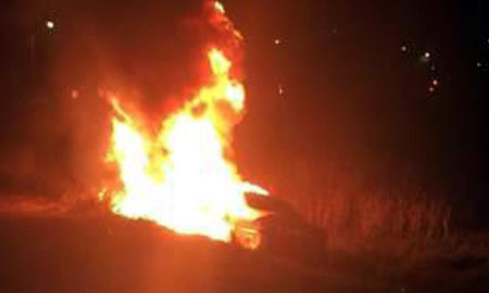A Honda Civic burns on Manchester Avenue at San Elijo Lagoon in Encinitas early Oct. 23. Sheriff's Deputy Steve Gusman is credited with saving the life of a driver trapped in the car. (San Diego County Sheriff's Department photo)