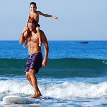 Summertime family surfing. (Photo by Filios Sazeides, Unsplash)