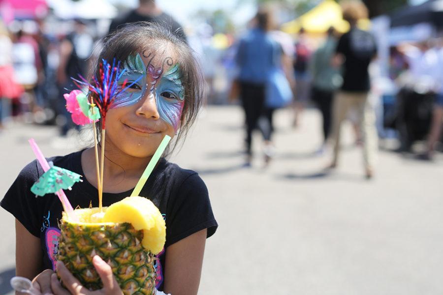 A young visitor to the Encinitas Spring Street Faire enjoys a piña colada April 29. (Photo by Jen Acosta)