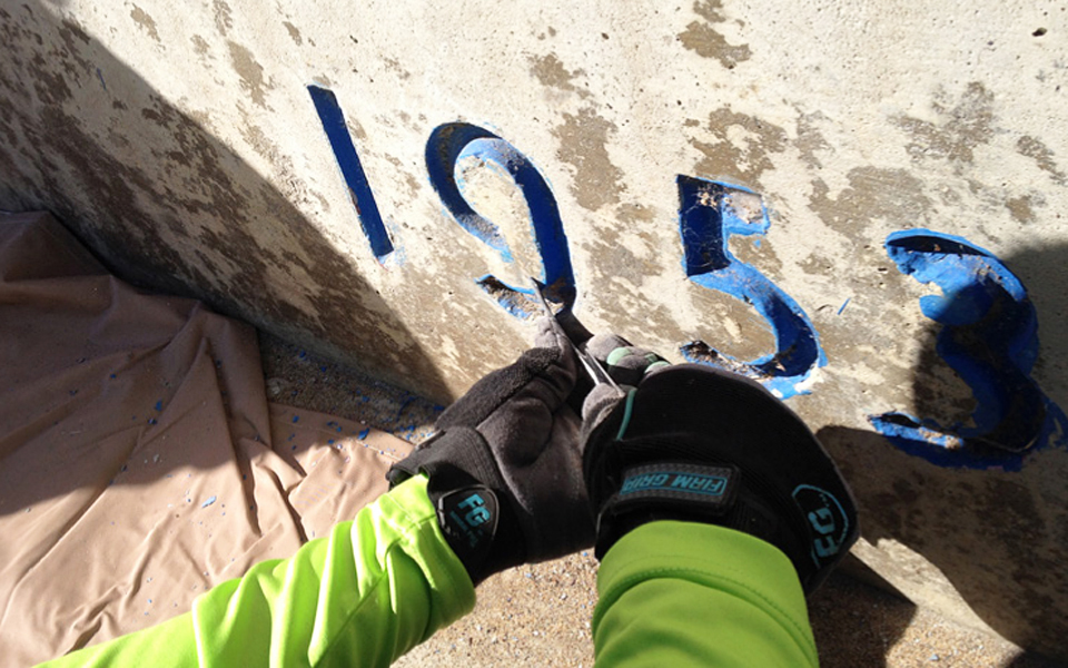 In this photo from an Encinitas Arts, Culture and Ecology Alliance impact report, a volunteer works on the former Pacific View school site's year stamp on an entrance wall at the Encinitas campus. (Encinitas Arts, Culture and Ecology Alliance photo)