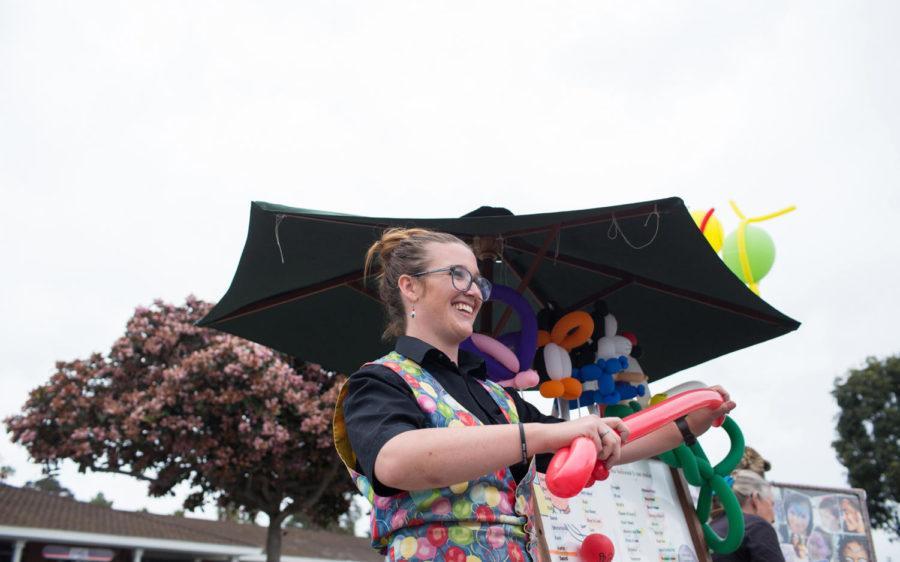 Cori, a professional balloon artist, creates a sword at the Encinitas Street Fair on Sunday, April 28. Cori has been a balloon artist for 12 years. (Photo by Cam Buker)