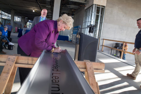 """CSU San Marcos President Karen Haynes signs a beam during a """"topping out"""" ceremony for the university's new Extended Learning building on Nov. 16, 2018. (CSUSM photo by Christine Vaughan)"""