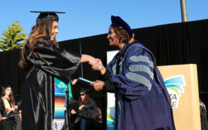 MiraCosta College President Sunita Cooke (right) congratulates a graduate May 24 at the Oceanside campus. (MiraCosta College photo by Alex Karvounis)