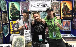 Carlsbad artist N.C. Winters (center) stands with assistants Seth Stewart (left) and Daniel Stewart (right) at Winters' booth at the 50th annual San Diego Comic-Con, which ran July 18-21 in downtown San Diego. (Photo by Meghan Lanigan)
