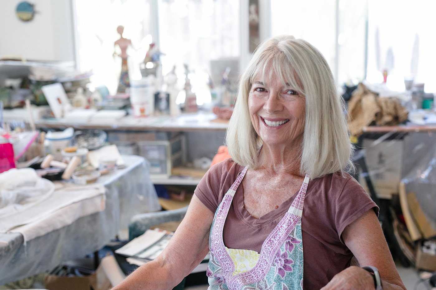 Encinitas artist Carla Funk sits among works in her studio July 2. (Photo by Jen Acosta)