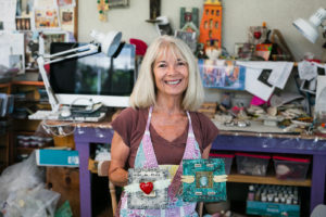 Encinitas artist Carla Funk shows two examples of work in her studio July 2. (Photo by Jen Acosta)