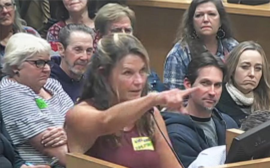 Cardiff resident Julie Thunder points toward the Encinitas city seal on the wall of the City Council chambers on Jan. 22 during the announcement of her run for mayor. (Encinitas city video feed)