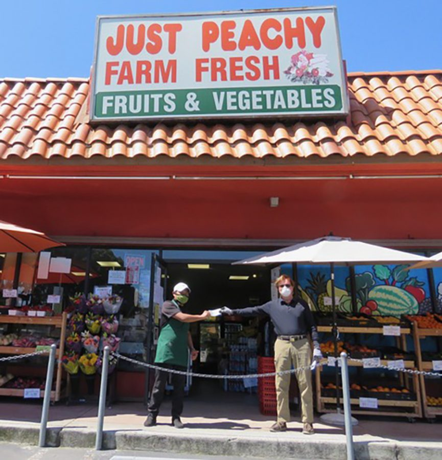 Robert Hemphill (right) delivers $500 checks to employees at Just Peachy Market in Leucadia on Wednesday, April 15, in recognition of the risks small businesses take in staying open during the COVID-19 coronavirus crisis. (Courtesy photo)