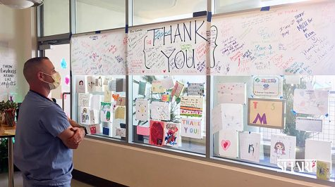 A Sharp COVID-19 caregiver looks at messages sent to the hospital's personnel from Santa Fe Christian Schools fifth graders. (Sharp Health News photo)