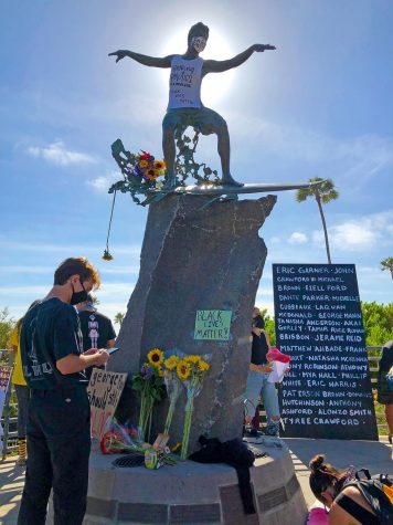 Encinitas residents gather under the Cardiff Kook statue on May 31 to protest the death of George Floyd in Minneapolis. (Photo courtesy of Scott Chatfield)