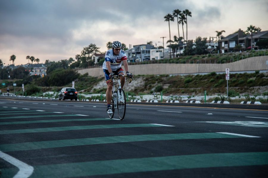 A cyclist rides through a portion of Encinitas' new protected bike lane in Cardiff on Wednesday, June 10, where riders can transition in and out of the automobile lane. (Photo by Jen Acosta)
