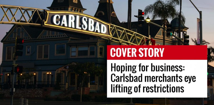 The historic Twin Inns building is shown at sunrise behind Carlsbad's downtown sign. (Photo by Art Wager, iStock Getty Images)