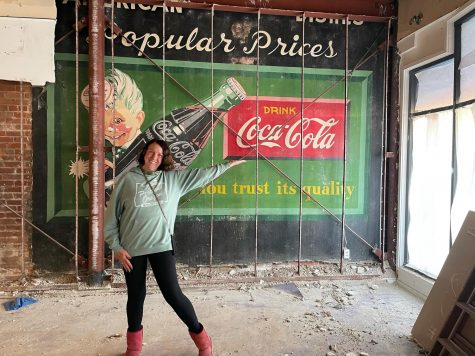 Eileen Burke, owner of Queen Eileen's Gift Baskets in downtown Encinitas, shows off a 1950s-era mural uncovered in her shop during remodeling in February. (Courtesy photo)