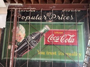 """A Coca-Cola sign recently uncovered at Queen Eileen's Gift Baskets in Encinitas features the """"Sprite Boy"""" character, which appeared in Coca-Cola advertisements from in the 1940s and '50s. (Courtesy photo)"""