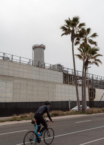 A cyclist heads south on Carlsbad Boulevard in front of the old Encina Power Station on April 10. (Photo by Jen Acosta)