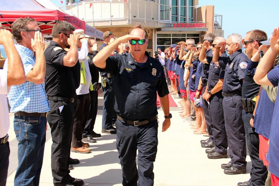 Encinitas Marine Safety Capt. Larry Giles salutes members of the city's public safety agencies, including fellow lifeguards, during his retirement celebration Tuesday, July 20, at Moonlight Beach. (Photo courtesy of Scott Chatfield)
