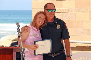 Encinitas Mayor Catherine Blakespear stands with city Marine Safety Capt. Larry Giles at his retirement celebration Tuesday, July 20, at Moonlight Beach. (Photo courtesy of Scott Chatfield)